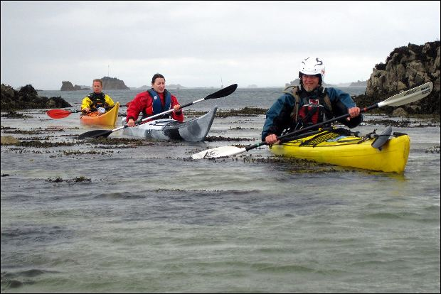 Drei Paddler an der Meeresküste